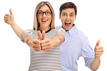Joyful young man and woman holding their thumbs up isolated on white background photo