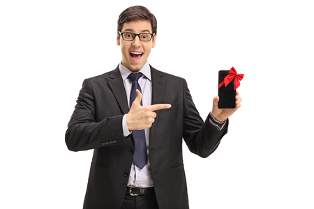 Businessman showing a phone wrapped with red ribbon as a gift and pointing isolated on white background photo