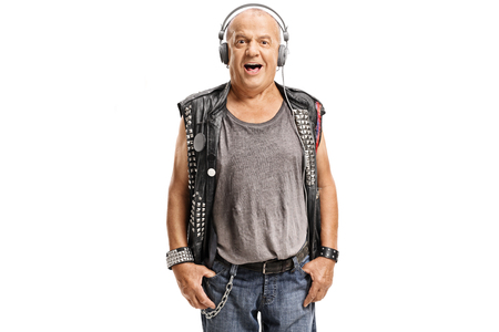 Elderly punker listening to music on headphones isolated on white background photo