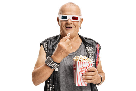 Elderly punker wearing a pair of 3D glasses and having popcorn isolated on white background photo