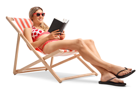 Young woman reading a book in a deck chair isolated on white background photo