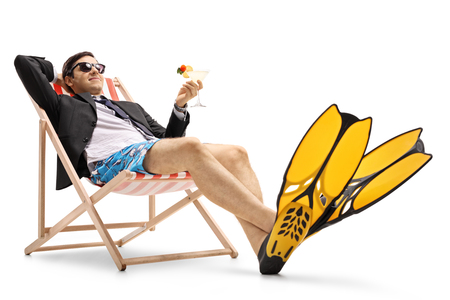 Businessman with swimming fins and a cocktail lying in a deck chair isolated on white background photo