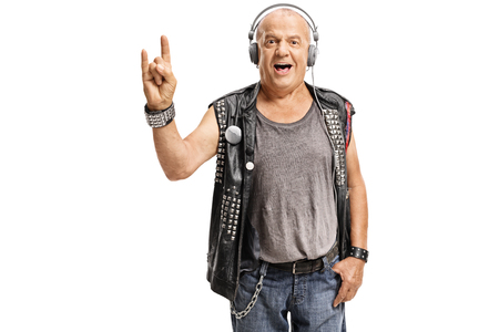 Elderly punker with headphones making a rock hand gesture isolated on white background photo