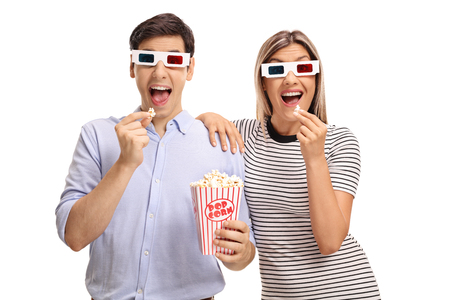 Young man and woman wearing 3D glasses and eating popcorn isolated on white background photo
