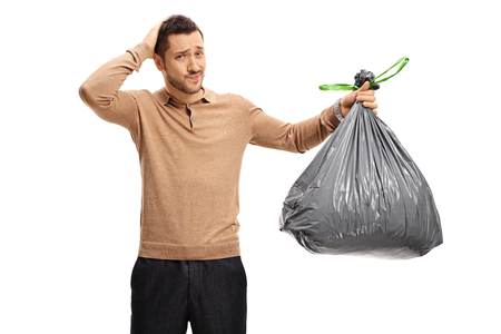 disgusted: Young man with a garbage bag holding his head in disbelief isolated on white background Stock Photo