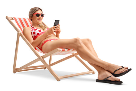 Young woman with a mobile phone in a deck chair isolated on white background