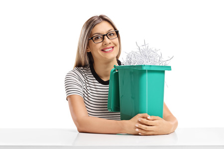Young woman with a garbage bin filled with shredded paper sitting at a table isolated on white background photo