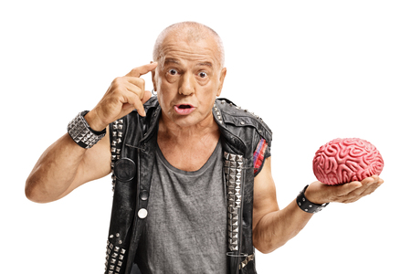 Elderly punker with a brain model holding a finger on his temple asking do you have a brain isolated on white background photo