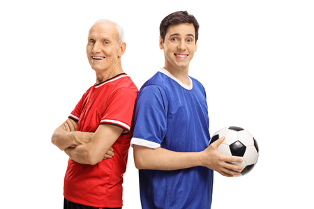 Elderly soccer player and a young player with a football looking at the camera and smiling isolated on white background photo