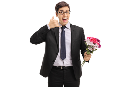 Cheerful businessman with flowers making a call me gesture isolated on white background photo