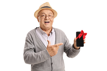 Mature man showing a phone wrapped with red ribbon as a gift and pointing isolated on white background photo