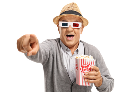 Mature man with popcorn and a pair of 3D glasses pointing and laughing isolated on white background photo