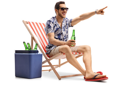 Tourist with a beer sitting in a deck chair next to a cooling box and pointing isolated on white background