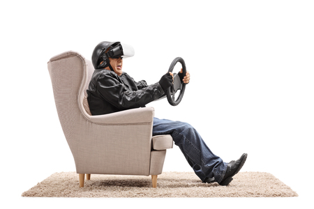 Elderly biker seated in an armchair using a VR headset and holding a steering wheel isolated on white background