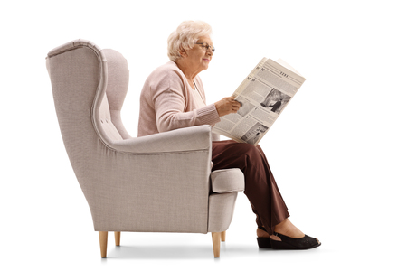 Profile shot of a mature woman sitting in an armchair and reading a newspaper isolated on white background