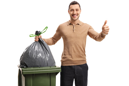 Young man throwing out the trash and making a thumb up gesture isolated on white background Stockfoto