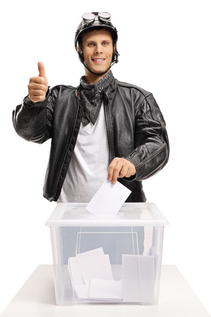 Biker casting a vote into a ballot box and making a thumb up gesture isolated on white background
