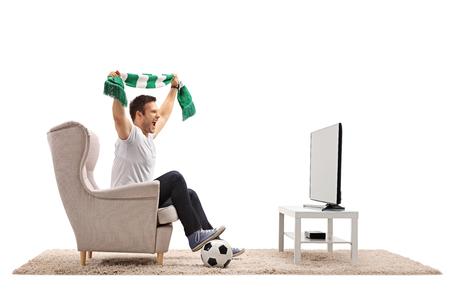 Eccitato calcio fan con una sciarpa seduta in una poltrona e guardando una partita in televisione isolato su sfondo bianco