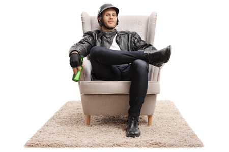 Biker with a bottle of beer sitting in an armchair and looking at the camera isolated on white background Banco de Imagens