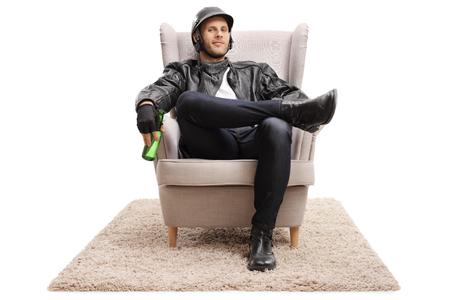 Motorista con una botella de cerveza sentado en un sillón y mirando a la cámara aislada en el fondo blanco Foto de archivo - 85946820