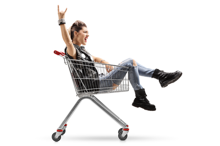 Punk girl riding in a shopping cart and making a rock hand gesture isolated on white background
