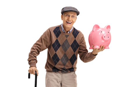 Cheerful senior with a piggybank and a cane isolated on white background 免版税图像