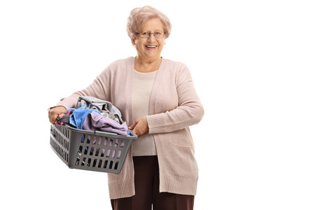 Elderly woman holding a laundry basket filled with clothes isolated on white background Stock Photo