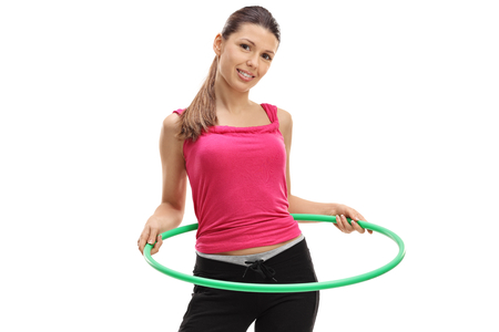 Female athlete exercising with a hula-hoop isolated on white background Stock Photo