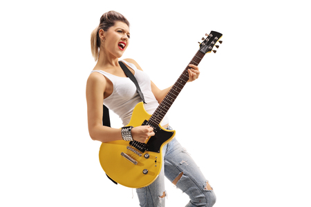 Punk girl playing an electric guitar isolated on white background