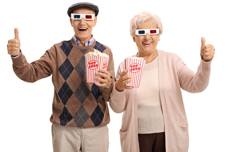 Cheerful seniors with 3D glasses and popcorn making thumbs up signs isolated on white background