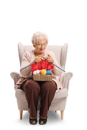 Bejaardezitting in een leunstoel en breien geïsoleerd op witte achtergrond