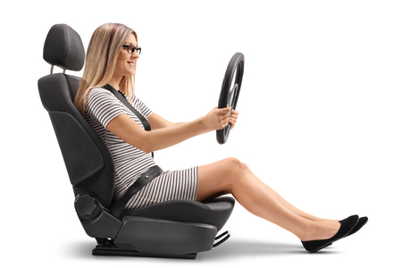 젊은 여자가 자동차 좌석에 앉아 및 흰색 배경에 격리 된 스티어링 휠 holing