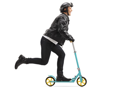 Full length profile shot of a biker riding a scooter isolated on white background Stock Photo