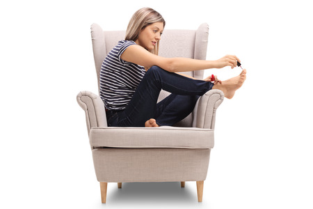 Young woman sitting in an armchair and doing her toenails isolated on white background