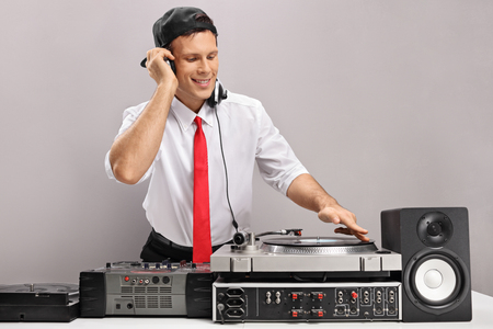audio mixer: Formally dressed guy playing music on a turntable isolated on gray background