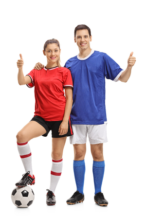 Full length portrait of a female and a male soccer players making thumb up gestures isolated on white background