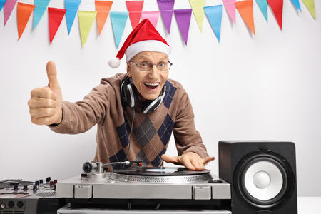 audio mixer: Elderly man with a christmas hat playing music on a turntable and making a thumb up sign against a wall with decoration flags