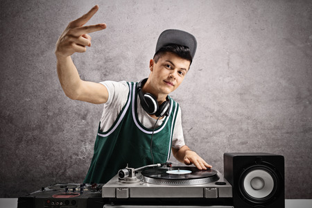 audio mixer: Teenage DJ making a pace sign against a rusty gray wall Stock Photo
