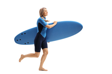 Full length profile shot of a woman in a wetsuit holding a surfboard and running isolated on white background Stock Photo