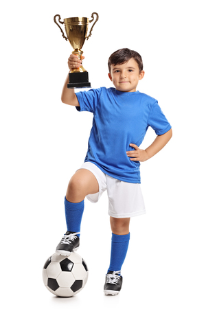 Full length portrait of a small boy in a blue jersey with a football and a gold trophy isolated on white background Foto de archivo