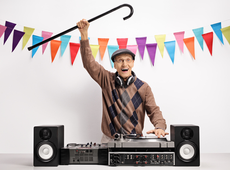 Overjoyed senior with a cane playing music on a turntable against a wall with decoration flags Standard-Bild