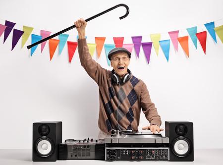 Berglücklicher Senior mit einem Stock, der Musik auf einer Drehscheibe gegen eine Wand mit Dekorationsflaggen spielt Standard-Bild - 87729254
