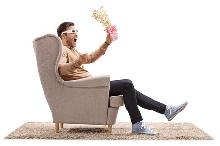 watching horror: Terrified guy with 3D glasses and popcorn sitting in an armchair isolated on white background
