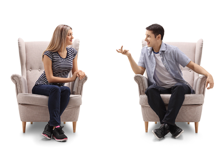 Young woman and a young man sitting in armchairs and talking isolated on white background Foto de archivo