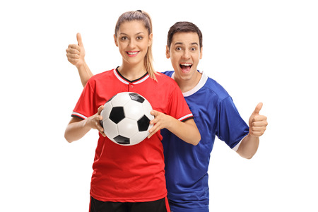 Female soccer player holding a football and a male soccer player holding his thumbs up isolated on white background
