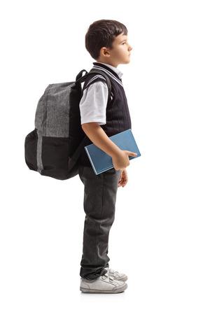 Volledige lengte profiel shot van een kleine schooljongen met een rugzak te wachten in de rij op een witte achtergrond