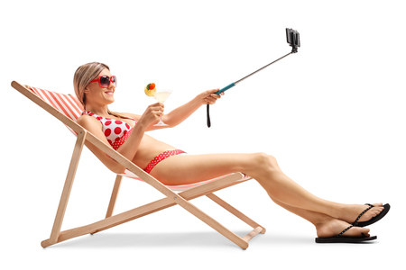 chairs: Young woman sitting in a deck chair and taking a selfie with a stick isolated on white background Stock Photo