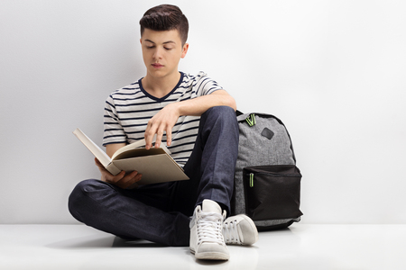 Teenage student reading a book and leaning against a wall