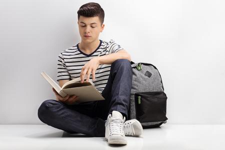 Estudiante adolescente leyendo un libro y apoyado contra una pared.