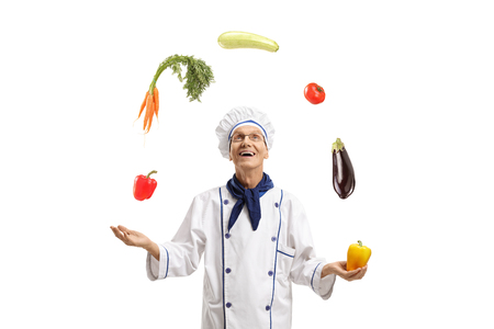 Elderly chef juggling with vegetables isolated on white background